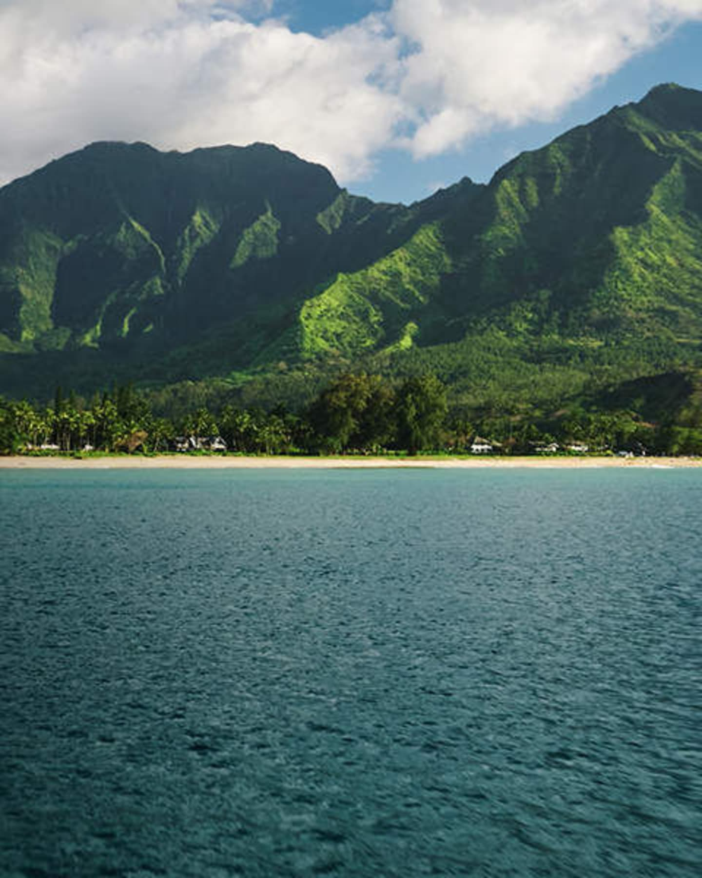 View across the sea towards a beach and green mountains.