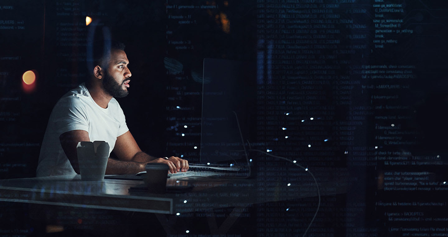 man sitting in a dark room in front of a computer screen