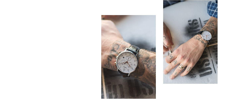 Dwa srebrne zegarki Waterbury z czarnymi skórzanymi paskami noszone przez dwie różne osoby oraz jeden srebrny Waterbury z szarym paskiem