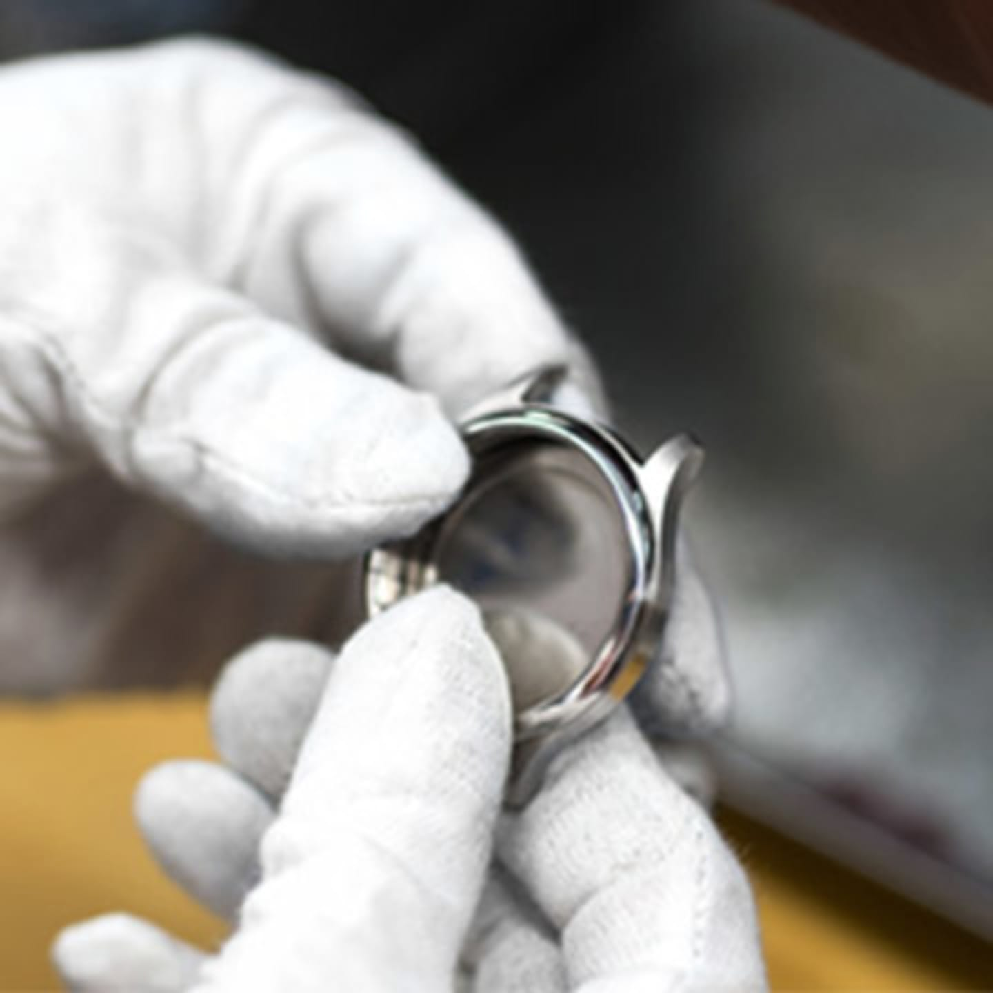 Watch maker with white gloves holding a silver watch body in their hands