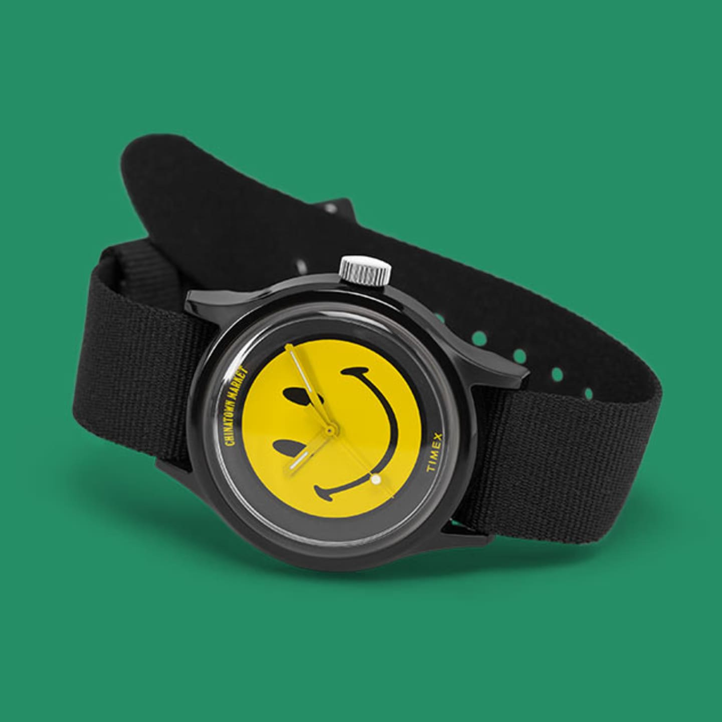 Black Chinatown Market Watch with Yellow Smiley Face Laying on Side